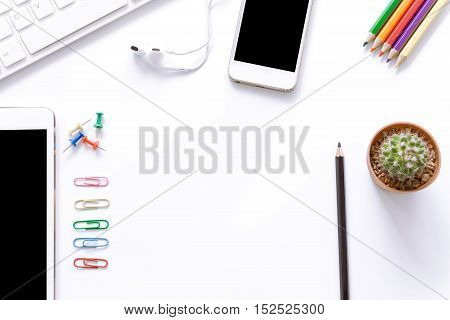 Office desk top view with smartphones, laptop and book / Office supplies Blank and pencil notebook and earphones on white background with copy space