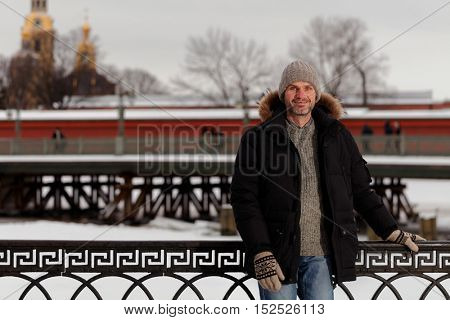 Mature man in winter clothes against St. Peter and Paul fortress in St. Petersburg, Russia