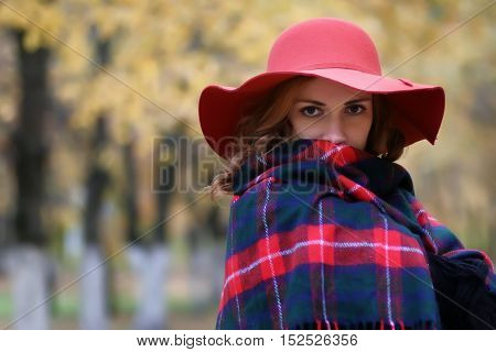 Serious woman in a red hat in autumn park