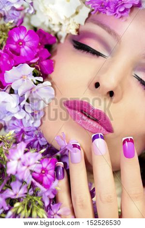 The French pink lilac manicure and makeup with phloxes on the girl.