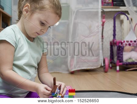 A little thoughtful girl busy with her constructor or toys sitting on the floor of a playroom. Interior shot with selective focus
