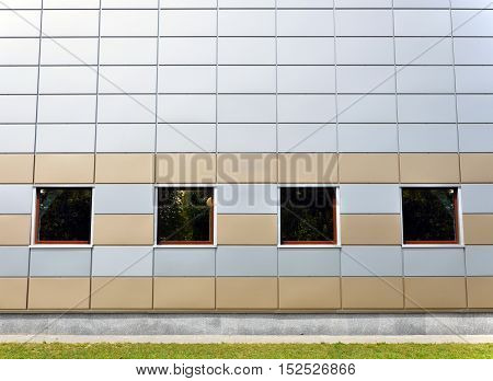 The front facade of a modern building of gray and yellow sandwich-panels with four square windows. Architectural background.