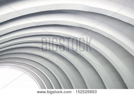 Architectural background. A modern white concrete arched ceiling in perspective. The same semicircular shape. The light in the distance.