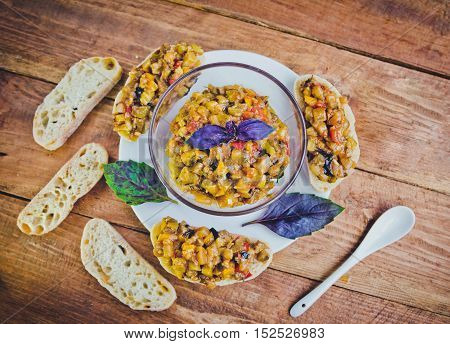 Roasted eggplant and tomatoes hot salad with basil, sandwiches with vegetable pate on wooden background
