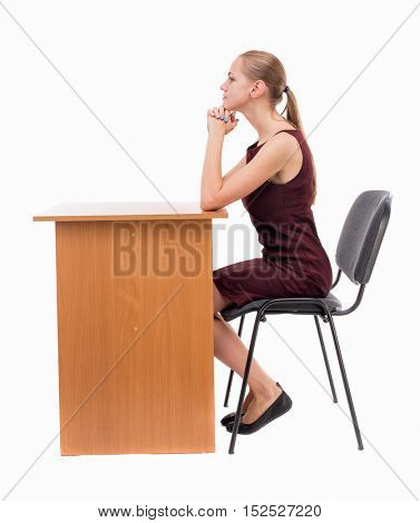 back view of woman sits by the table and looks.  Rear view people collection.  backside view of person.  Isolated over white background. A girl in a burgundy dress sitting at the table.