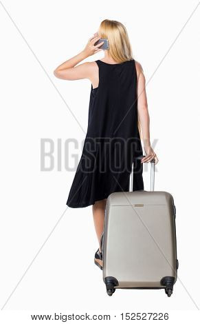 Back view of woman with suitcase talking on the phone.   backside view of person. Isolated over white background. Long-haired blonde in a black dress talking on the phone holding a suitcase.