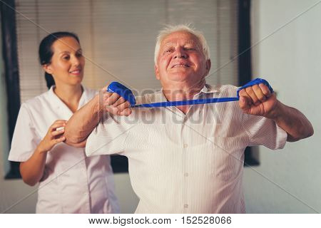 Senior man doing exercises using a strap to extend and strenthen her neck and shoulder muscles