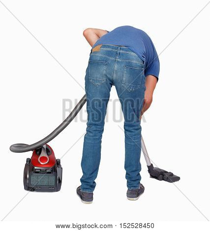 Rear view of a man with a vacuum cleaner. He is busy cleaning. Rear view people collection.  backside view of person.  Isolated over white background. The guy in the blue shirt vacuums.