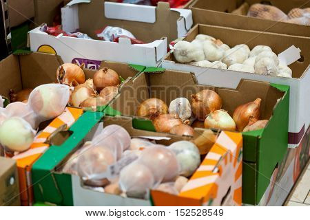Onions and garlic in boxes in supermarket