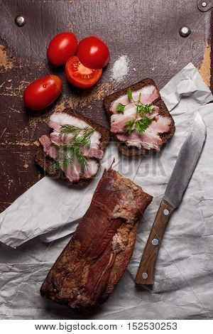 Smoked Bacon With Rye Black Bread And Cuted Tomatoes On The Packaging Paper. Old Knife With Wooden H