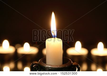 Set of lighting candles in a row against dark background