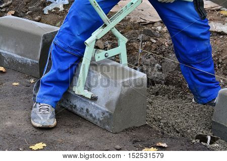 Worker lifts concrete curb with a manual lifting tool. Concrete kerb installation at sidewalk edging.