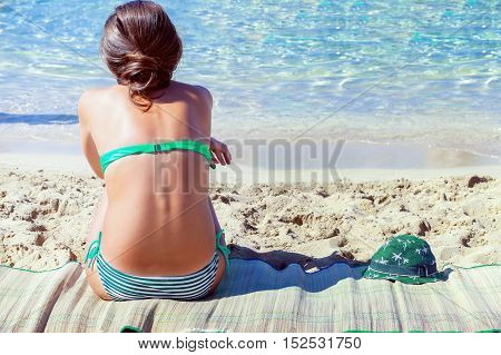 Woman sitting at the beach of blue sea
