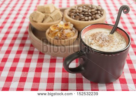 Black coffee with rich crema in a black ceramic mug cane sugar caramel and coffee beans in the wooden bowls are on a background of red and white checkered cloth
