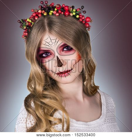 Beautiful young woman in day of the dead mask skull face art, over gray background