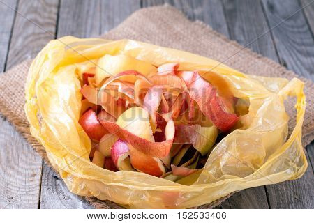 Peeled apples in a plastic bag on a wooden background