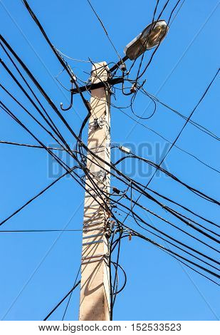 Electric power post with wire against bright blue sky