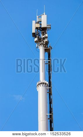 Telecommunication tower for mobile phone with antennas over a blue sky. Distribution function of contract mobile phones