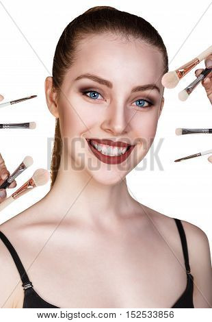Beautiful woman with make-up brushes near attractive face, over white background
