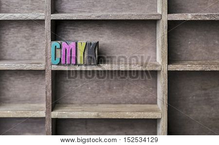 old wooden printers type forming the word CMYK
