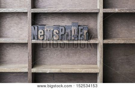 old wooden printers type forming the word Newspaper