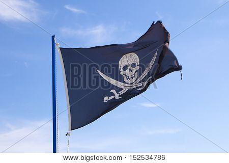Pirate flag waving on cloudy blue sky