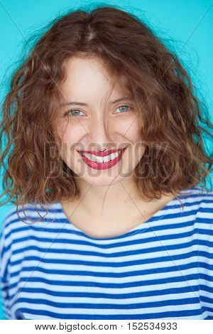 Close up portrait of young beautiful girl smiling to camera. Hipster young woman with natural makeup and curly hair on blue background, not isolated.