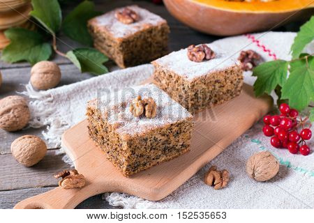 Sliced pumpkin pie with nuts on a wooden background