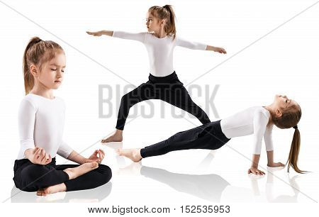 Little girl doing yoga exercises over white background