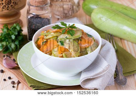Vegetable stew. Zucchini and carrots on a wooden background