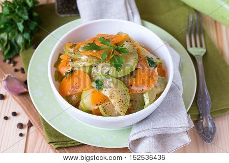 Zucchini braised with vegetables on a wooden background