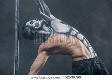 Strong pole dancer with horrific body-art next to a pylon in the dark studio with a smoke on the background. He holds the pylon with the hands and looks up. Man wears black pants. Horizontal.