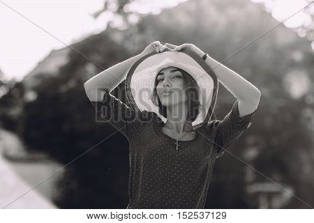 beautiful young model standing in a hat outdoors