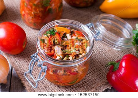Canned vegetable salad in glass on a wooden background