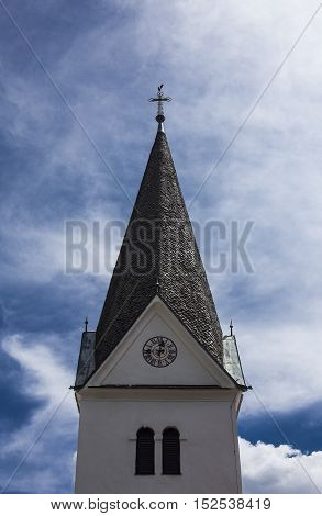 Christian church small tower with a cross and a clock.