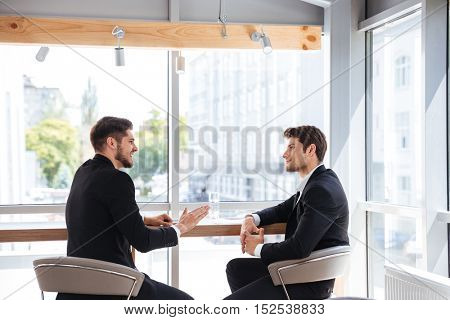 Two handsome young businessmen sitting and talking in office