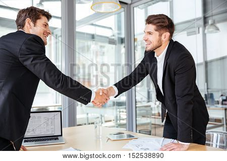 Two cheerful successful young businessmen shaking hands on business meeting