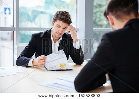 Two thoughtful young businessmen working with business plan in office