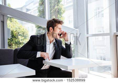Mad angry young businessman sitting in cafe and shouting in cell phone
