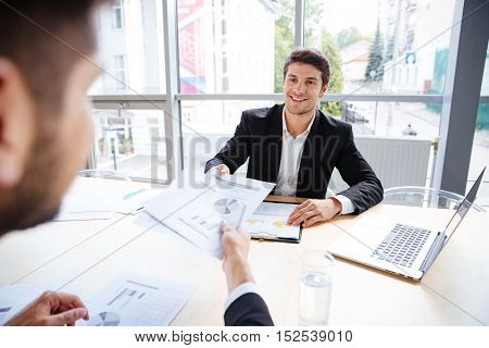 Two successful young businessmen sitting and creating business plan on meeting in office
