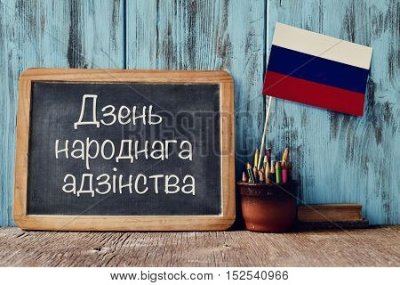 a chalkboard with the text National Unity Day written in Russian, a pot with pencils, some books and the flag of Russia, on a wooden desk