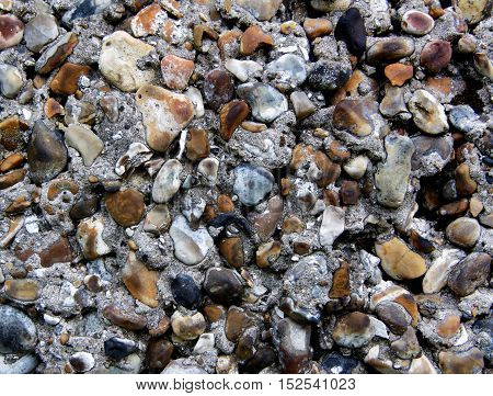 Background of Old Cobblestone Wall with Cracked Concrete Small Stones Natural Dirties closeup Outdoors