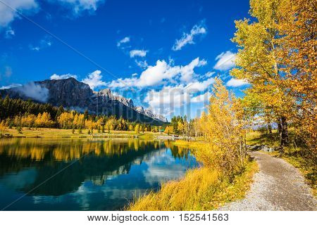 The concept of hiking. Path around the lake. Canmore, near Banff Park. Majestic mountains and autumn aspens reflected in the water