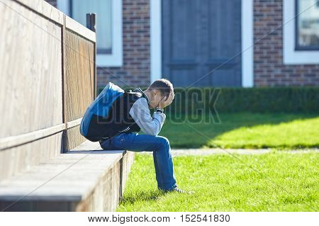 schoolboy crying in the yard of the school negative emotion