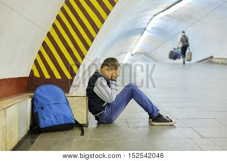 schoolboy crying in the subway station negative emotion