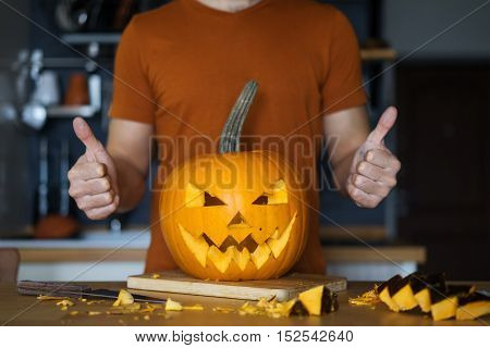The carved head of a pumpkin jack in the kitchen. The man in the background shows gesture thumbs up.