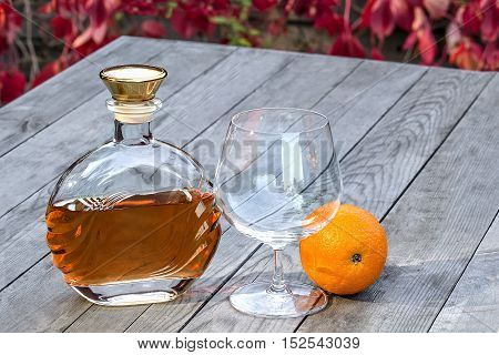 Bottle of brandy and a snifter with orange on the old table in autumn garden's