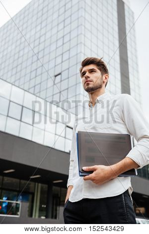 Confident young businessman holding folder with documents standing near business center