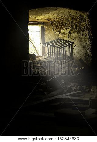 old window in abandoned place with a cage.