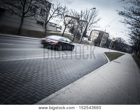 Car passing on Gdansk road on overcast day